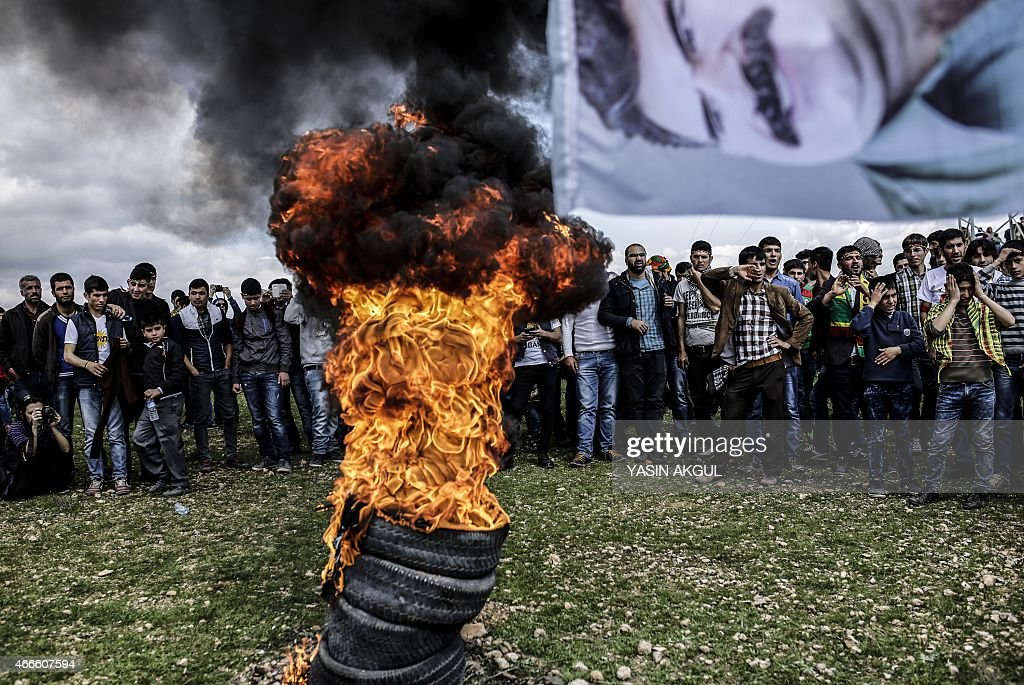 A flag bearing a portrait of jailed Kurdish leader <a gi-track='captionPersonalityLinkClicked' href=/galleries/search?phrase=Abdullah+Ocalan&family=editorial&specificpeople=658599 ng-click='$event.stopPropagation()'>Abdullah Ocalan</a> flies near a fire as Kurdish people gather to celebrate Newroz, which marks the arrival of spring and the new year, in the Turkish town of Suruc, across the border from the Syrian town of Kobani, on March 17, 2015. AFP PHOTO / YASIN AKGUL