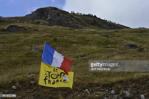A flag bearing the Tour de Franced logo and a French national flag are pictured along the road during the 1105 km twentieth stage of the 102nd...