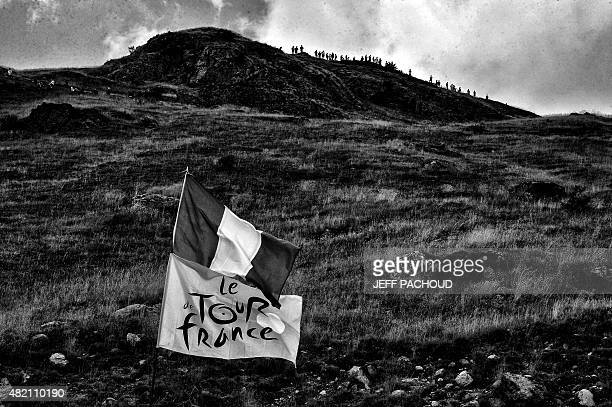 VERSION A flag bearing the Tour de Franced logo and a French national flag are pictured along the road during the 1105 km twentieth stage of the...