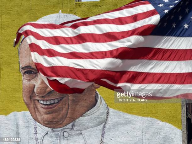 A US flag blows in the wind in front of a mural of Pope Francis across the street from Madison Square Garden in New York September 21 2015 as the...