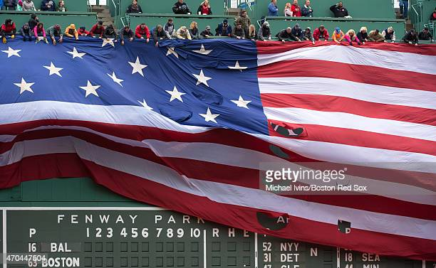 A flag drops over the left field wall during the national anthem before a game between the Boston Red Sox and the Baltimore Orioles at Fenway Park in...