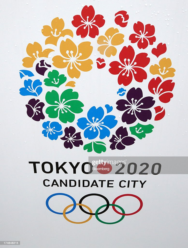 A flag featuring the campaign logo for Japan's bid for the 2020 Olympic and Paralympic Games is displayed during a media tour in Tokyo, Japan, on Monday, July 29, 2013. Tokyo, the front-runner city to host the 2020 Olympics, is planning its biggest housing complex in 42 years to lodge athletes, a move that could benefit developers such as Shimizu Corp. and Mitsubishi Estate Co. Photographer: Tomohiro Ohsumi/Bloomberg via Getty Images