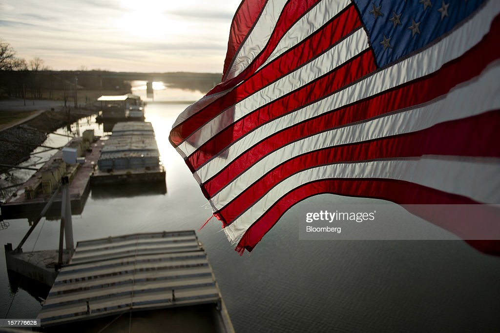 A U.S. flag flies above barges filled with soybeans on the Kaskaskia River, a tributary of the Mississippi River, at Gateway FS in Evansville, Illinois, U.S., on Wednesday, Dec. 5, 2012. U.S. farmers, facing aftershocks of the worst drought in 50 years, are improvising alternative plans for corn, soybeans and other grains that won't be moving to world markets as the Mississippi River dries up. Photographer: Daniel Acker/Bloomberg via Getty Images