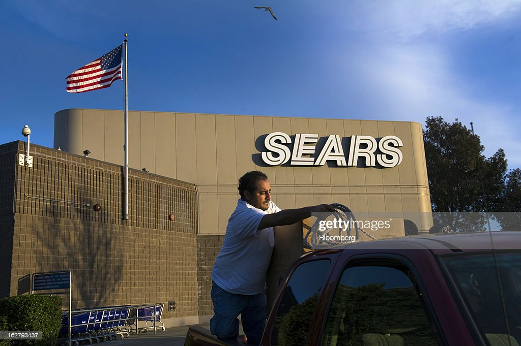 A U.S. flag flies as customers secure a new washing machine that was purchased at a Sears Holdings Corp. store in the back of a pickup truck in Richmond, California, U.S., on Tuesday, Feb. 26, 2013. Sears Holdings Corp. is expected to release earnings data on Feb 28. Photographer: David Paul Morris/Bloomberg via Getty Images