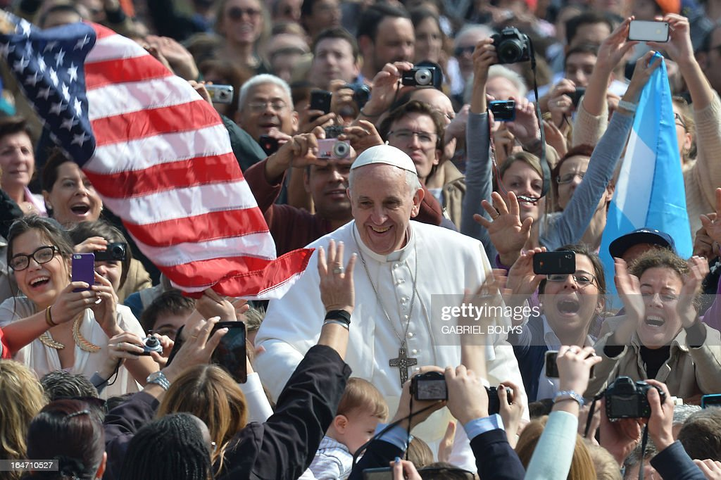 A US flag flies as Pope Francis waves to the crowd before audience at St Peter's square on March 27, 2013 at the Vatican.