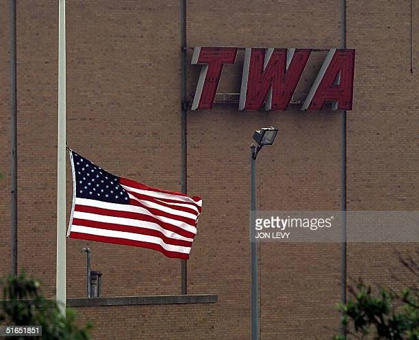 US flag flies at half mast 17 July outside a TWA hangar at John F Kennedy Airport in New York A memorial service for the victims of TWA Flight 800...