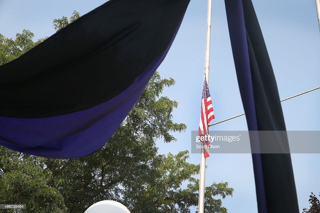 A flag flies at half mast and mourning bunting hangs across the front of the Fox Lake Police Department in memory of Lt Joe Gliniewicz on September 2...