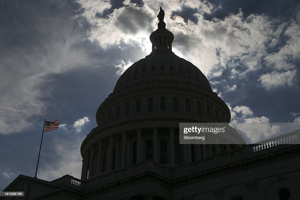 A U.S. flag flies at the U.S. Capitol in Washington, D.C., U.S., on Thursday, Sept. 26, 2013. The Senate is accelerating debate on a bill that would avert a U.S. government shutdown as Senate Republicans sought to buy time for their House counterparts to take another swipe at President Barack Obama's health-care law. Photographer: Andrew Harrer/Bloomberg via Getty Images