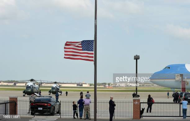 A US flag flies halfmast as Marine One helicopter with US President Barack Obama and First Lady Michelle Obama on board prepare to take off from...