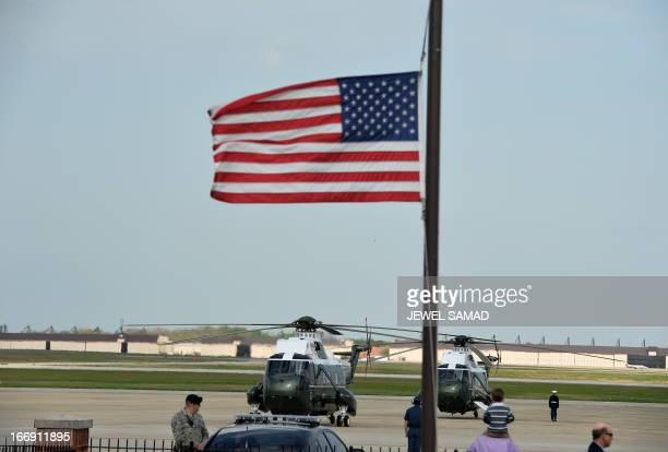 A US flag flies halfmast as Marine One with US President Barack Obama and First Lady Michelle Obama on board prepare to take off from Andrews Air...
