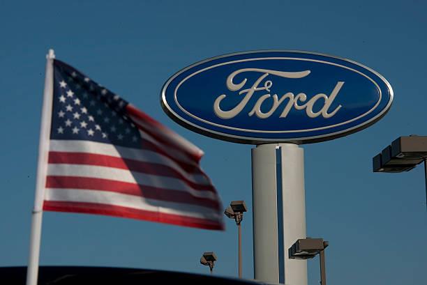 A US Flag Flies Near Ford Motor Co Logo At Rod Baker Dealership