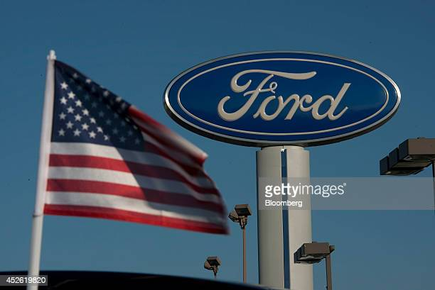 A US flag flies near a Ford Motor Co logo at Rod Baker Ford dealership in Plainfield Illinois US on Wednesday July 23 2014 Ford Motor Co's...
