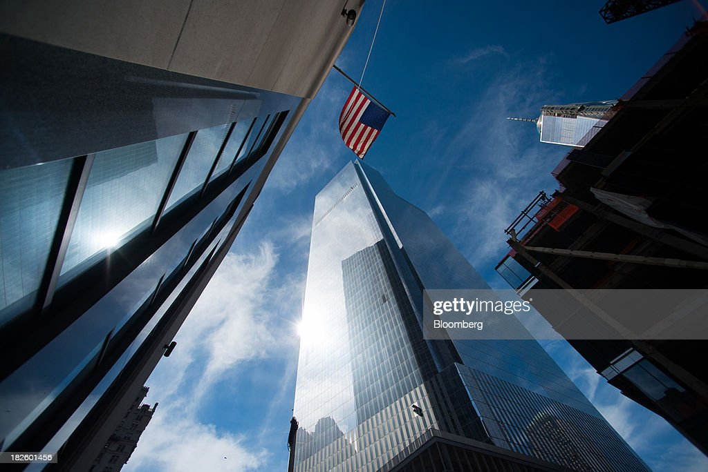 A U.S. flag flies near the 4 World Trade Center building, managed by Silverstein Properties Inc., center, in New York, U.S., on Wednesday, Sept. 25, 2013. Real estate developer Larry Silverstein cant recoup any of the $1.2 billion recovered by World Trade Center insurers in settlements with airlines and airport security companies over the Sept. 11, 2001, terrorist attack that destroyed the office complex, a judge ruled. Photographer: Craig Warga/Bloomberg via Getty Images