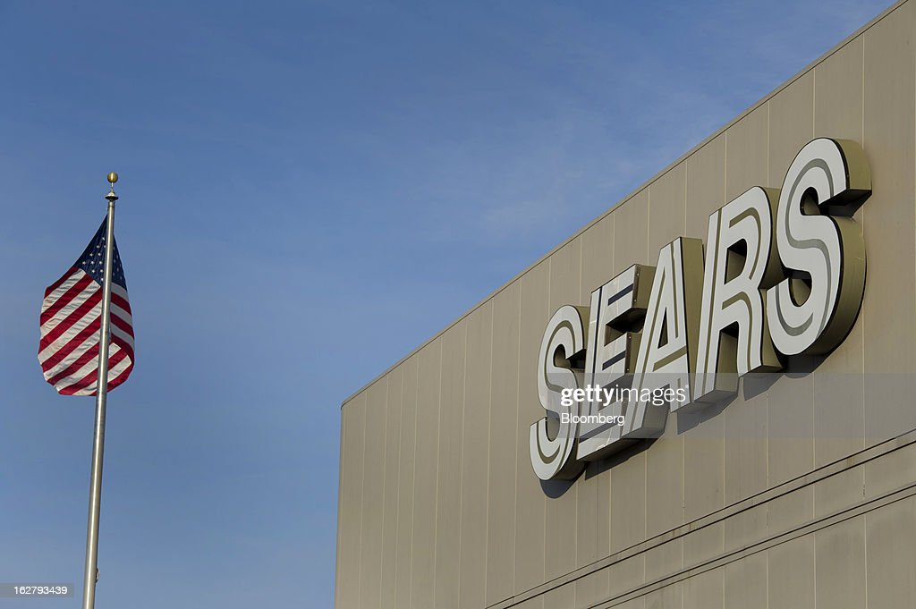 A U.S. flag flies next to Sears Holdings Corp. signage displayed outside of a store in Richmond, California, U.S., on Tuesday, Feb. 26, 2013. Sears Holdings Corp. is expected to release earnings data on Feb 28. Photographer: David Paul Morris/Bloomberg via Getty Images