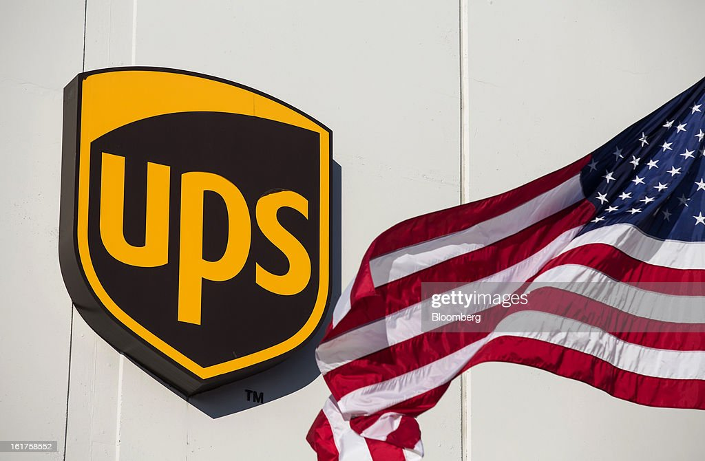 A U.S. flag flies next to United Parcel Service (UPS) signage at the distribution center in Sacramento, California, U.S., on Thursday, Feb. 14, 2013. 100 UPS delivery all-electric vehicles, developed by Electric Vehicles International (EVI), have been deployed this week and are said to eliminate the use of 126,000 gallons of fuel per year. Photographer: Ken James/Bloomberg via Getty Images