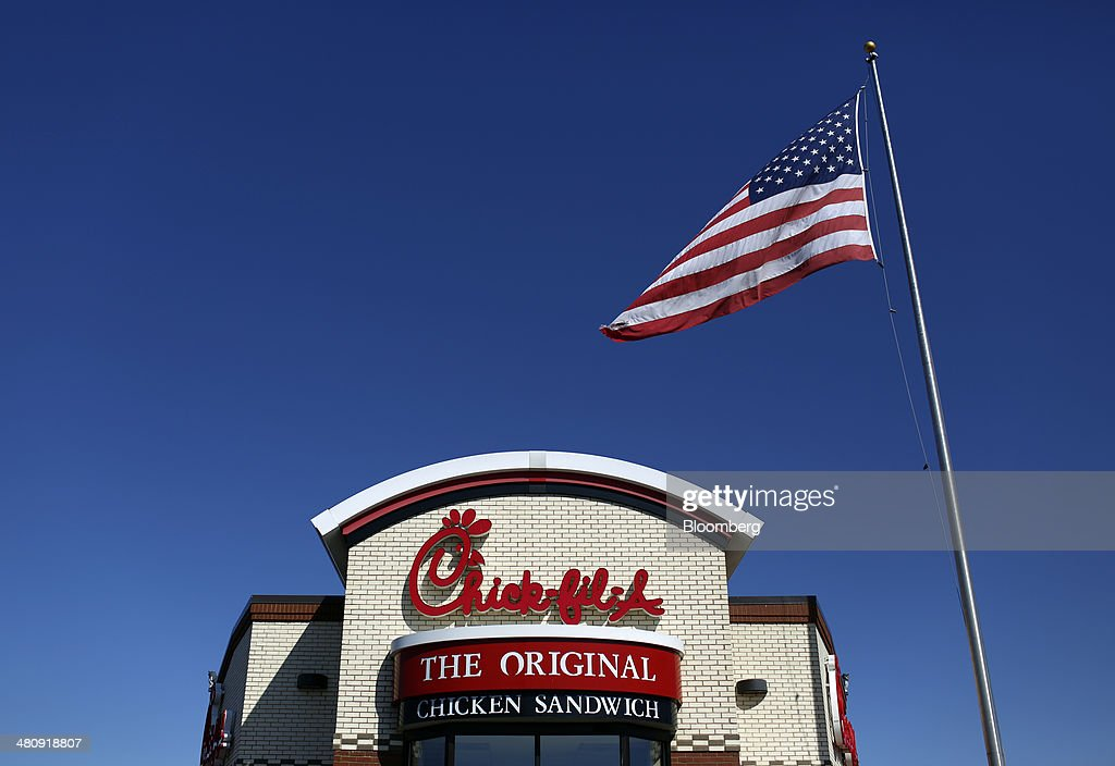 A U.S. flag flies outside a Chick-fil-A Inc. restaurant in Bowling Green, Kentucky, U.S., on Tuesday, Mar. 25, 2014. The U.S. economy grew more rapidly in the fourth quarter than previously estimated as consumer spending climbed by the most in three years, showing the expansion had momentum heading into this years harsh winter. Photographer: Luke Sharrett/Bloomberg via Getty Images