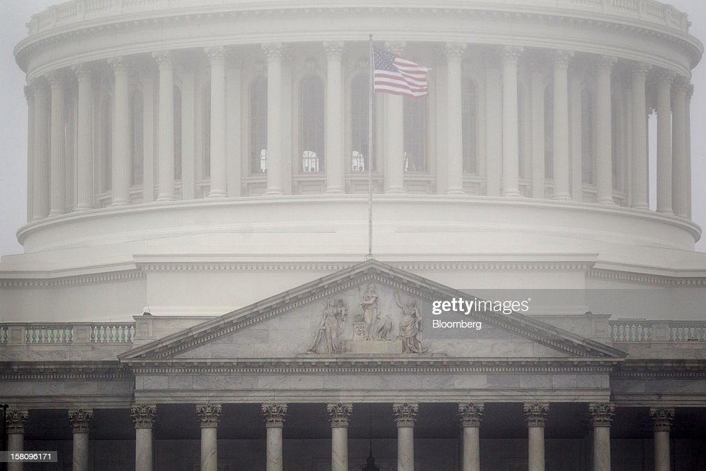 A U.S. flag flies outside the Capitol as it is surrounded by fog in Washington, D.C., U.S., on Monday, Dec. 10, 2012. Lawmakers from both parties are leaving rhetorical room for a split-the-difference agreement with President Barack Obama on a U.S. budget deal . Photographer: Andrew Harrer/Bloomberg via Getty Images