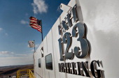 A US flag flies outside the control room of the Unit Drilling Co crude oil rig 123 during operations outside Watford City North Dakota US on Tuesday...