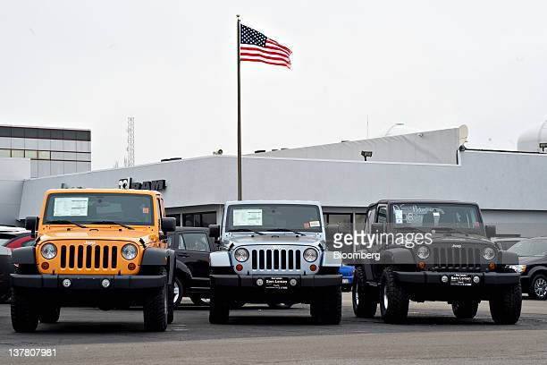 A US flag flies over 2012 Jeep Wrangler vehicles on display at Sam Leman Chrysler Dodge Jeep in Peoria Illinois US on Friday Jan 27 2012 Cars and...