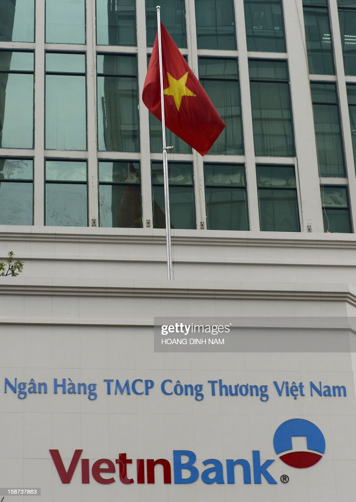 A flag flies over the facade of the main office building of the local commercial bank VietinBank in downtown Hanoi on December 27, 2012. Japan's biggest bank Mitsubishi UFJ on December 27 bought a 20 percent stake worth 743 million USD in state-owned VietinBank, the largest-ever foreign investment in Vietnam's banking sector. AFP PHOTO/HOANG DINH Nam