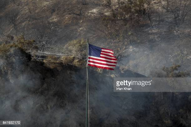 CA SEPTEMBER 2 2017 A flag flutters against the charred hillside along La Tuna Canyon Road that is closed to traffic La Tuna brush fire in the...