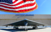 A US flag flutters in the wind beside a B2 Stealth Bomber at the Palmdale Aircraft Integration Center of Excellence in Palmdale California on July 17...