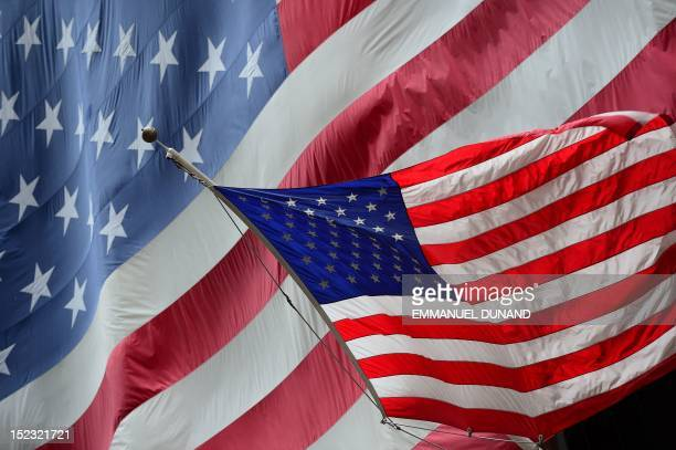 A US flag flutters in the wind in front of a large US flag in New York September 18 2012 AFP PHOTO/Emmanuel Dunand