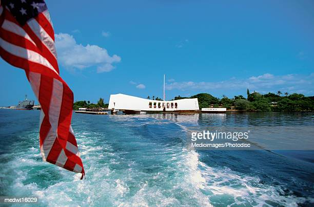 US Flag flying off the back of the USS Arizona in Pearl Harbor, Oahu, Hawaii, USA