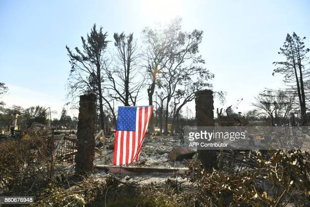 A US flag hangs from the remains of a burned property in Santa Rosa California on October 12 2017 Hundreds of people are still missing in massive...