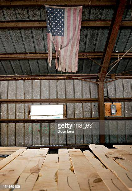 A US flag hangs over a conveyor belt of hard maple boards at the Nicolet Hardwoods Corp lumber mill in Laona Wisconsin US on Wednesday Oct 10 2012...