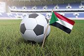 Sudan flag in stadium field with soccer football