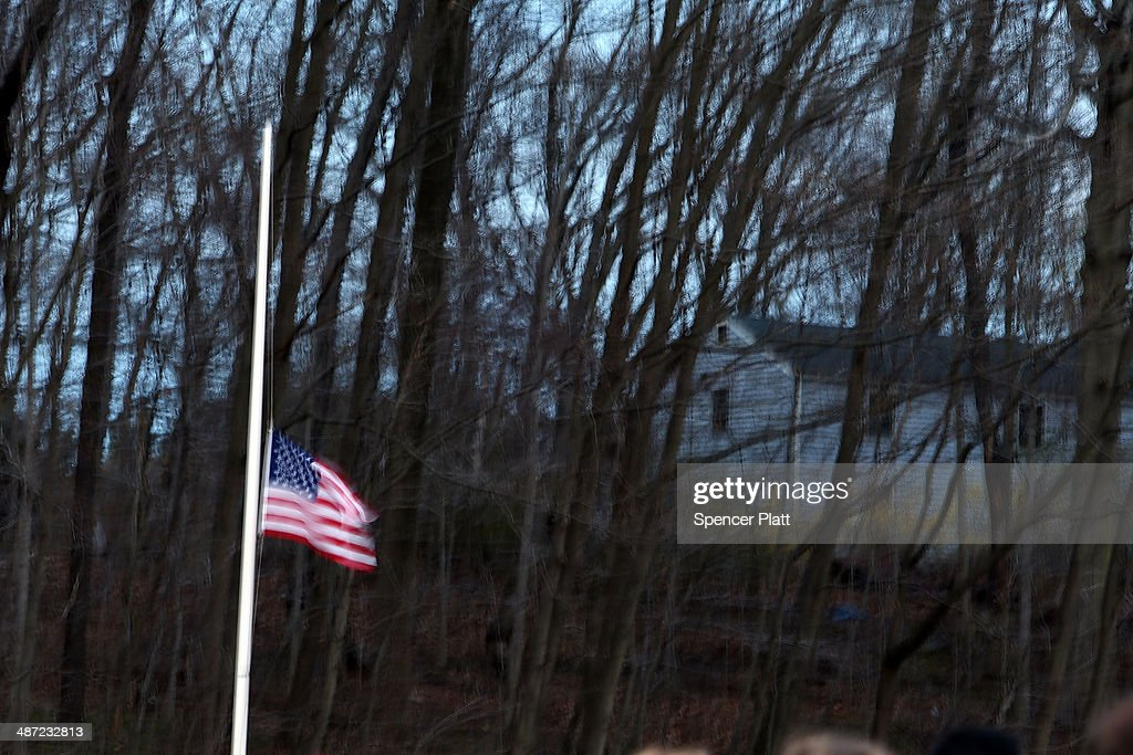A flag is flown at half mast during a candlelight vigil attended by hundreds at Jonathan Law High School after the death of Maren Sanchez who was...