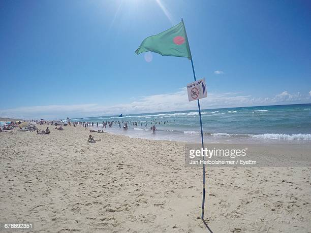 Flag Of Bangladesh And People At Beach Against Sky On Sunny Day