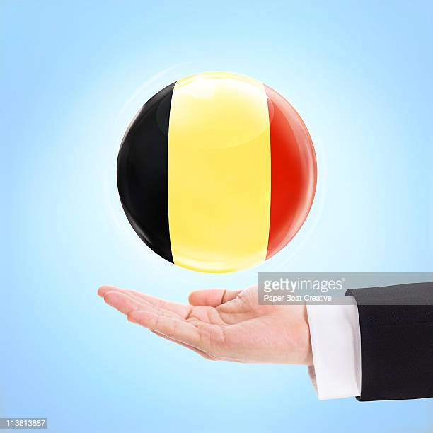 Flag of Belgium being supported by a hand