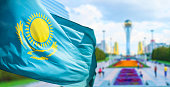 Wind develops flag of the Republic of Kazakhstan in bacground Astana