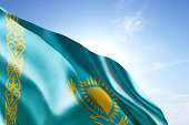 Flag of Kazakhstan waving in the wind. Blue sunny sky in the background. Horizontal orientation.