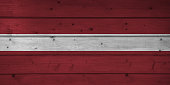 Flag of Latvia on wooden background, surface. Wooden wall, planks. National flag and symbol.