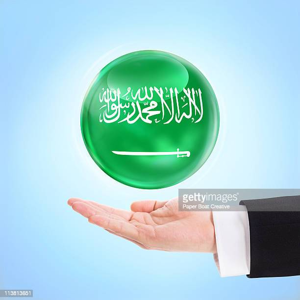 Flag of Saudi Arabia being supported by a hand
