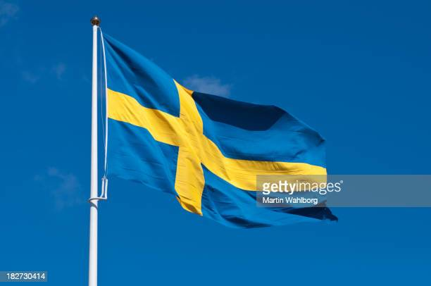 Flag of Sweden on flagpole rippling in wind against blue sky