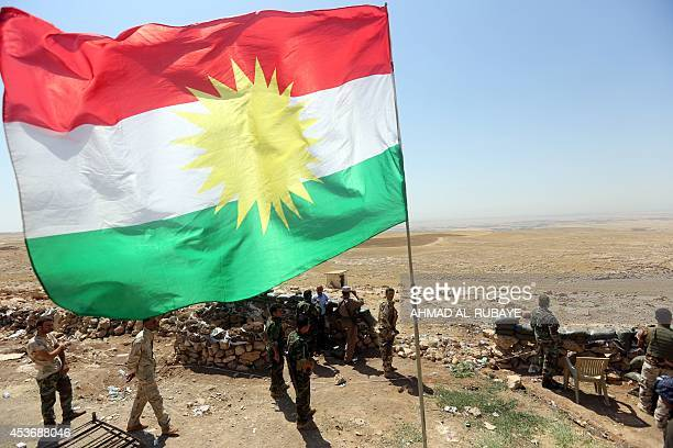 A flag of the autonomous Kurdistan region flies as Iraqi Kurdish Peshmerga fighters take position to monitor the area from their front line post in...