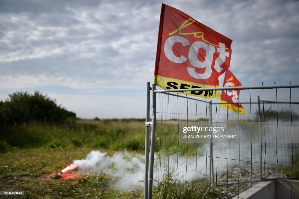 A flag of the CGT union is seen next to a flare as striking workers block the access to an oil depot near the Total refinery of Donges, western France, on May 25, 2016 to protest against the government's planned labour law reforms. France has been using strategic fuel reserves for two days in the face of widespread blockades of oil depots by union activists, the head of the oil industry federation said on May 25, 2016. / AFP / JEAN
