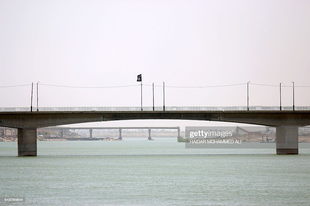 A flag of the Islamic State group (IS) flutters on Fallujah's new bridge across the Euphrates River on June 27, 2016 in the western part of the city which is located 50 kilometres (30 miles) from the Iraqi capital Baghdad, after Iraqi government forces retook the embattled city from IS. Iraqi forces took the Islamic State group's last positions in the city of Fallujah on June 26, 2016, establishing full control over one of the jihadists' most emblematic bastions after a month-long operation. ALI