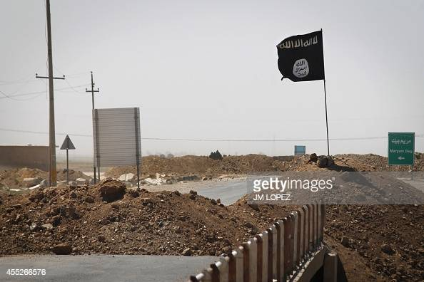 A flag of the Islamic State is seen on the other side of a bridge at the frontline of fighting between Kurdish Peshmerga fighters and Islamist...