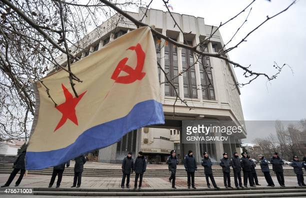 A flag of the Russian Navy hangs from a tree as policemen stand guard in front of the local parliament building on February 28 2014 in Simferopol...
