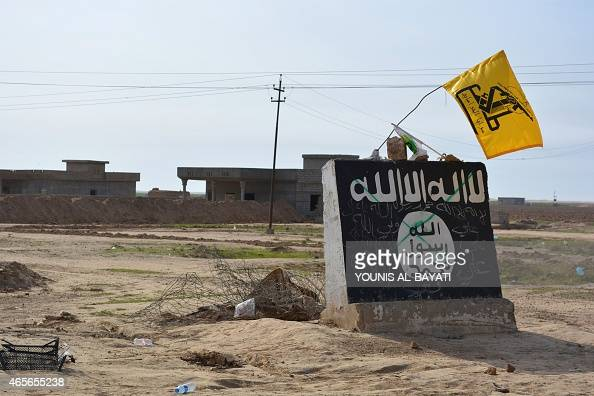 A flag of the Shiite Hezbollah militant group flutters over a mural depicting the emblem of the Islamic State group in AlAlam village northeast of...