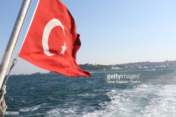 Flag Of Turkey Waving Over Sea Against Clear Sky