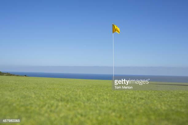 Flag on golf course overlooking ocean