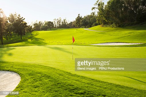 Flag on golf course surrounded by sand traps