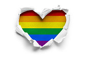 Heart shaped hole torn through paper, showing satin texture of flag of LGBT. Isolated on white background