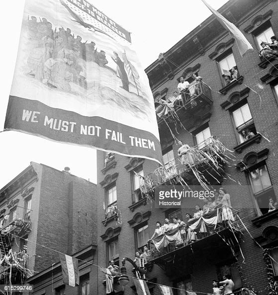 Flag raising ceremony in the rain in honor of Mott Street boys in the American Armed Forces New York New York August 1942